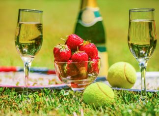 Tennis game. Strawberries, champagne and tennis balls with rackets on the green grass. Sport, recreation concept